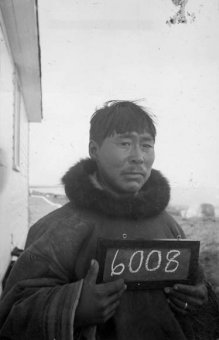 A black-and-white photograph of an Inuit guy holding a tiny chalkboard because of the number 6008.