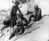 Aboriginal males sharpening rock axes on level stone. PH 416/43, ABC TV Collection, Northern Territory Library.